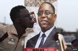 FILE - A man sticks out his tongue next to an election poster of incumbent Senegalese President Macky Sall in Pikine, Senegal, Feb. 7, 2019.