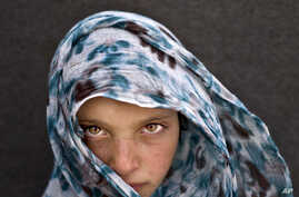 Syrian refugee girl Amna Zughayar, 9, from Deir el-Zour, Syria, poses for a picture at an informal tented settlement near the Syrian border on the outskirts of Mafraq, Jordan, March 13, 2016.