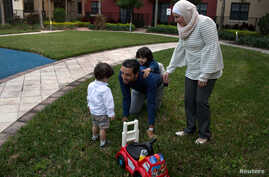 Temporary Protected Status (TPS) holders Mohammad Alala his wife Dania, both from Syria and their two U.S. born children Taim and Amr play at a playground at their home in Miramar, Florida, U.S., Jan. 24, 2018.