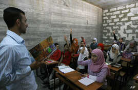 FILE - A Syrian teacher (L) is seen teaching at a school built for Syrian refugees in the southern port city of Sidon, Lebanon.