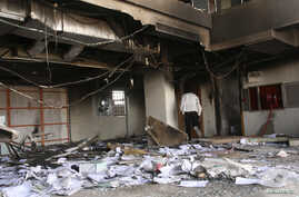 A man walks in a burnt bank during protests over fuel subsidy cuts in Khartoum, Sept. 26, 2013.