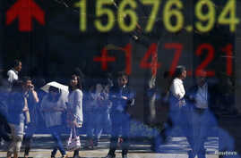 People are reflected in an electronic board displaying rises in Dow Jones Industrial Average outside a brokerage in Tokyo September 19, 2013. Japan's Nikkei share average rose to an eight-week high on Thursday morning, led by commodity stocks after t
