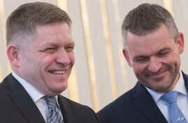 FILE - Outgoing Slovakian Prime Minister Robert Fico (L) and  his replacement as new prime minister, Peter Pellegrini, smile at the Presidential palace in Bratislava on March 15, 2018.