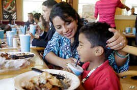 FILE - Wendlin Giron talks with her son, Uziel Enoc Banegas Giron, 5, as they eat a complimentary lunch at a Share a Meal event for homeless families hosted at a local restaurant by the Miami Police Department, Dec. 13, 2016, in Miami. Giron is an im
