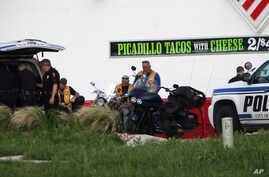 Police detain and watch members of various motorcycle clubs near a Twin Peaks restaurant in Waco, Texas, Sunday, May 17, 2015.