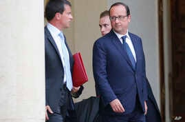 French prime minister Manuel Valls, left, leaves with French President Francois Hollande after a meeting at the Elysee Palace in Paris, Monday, Aug. 25, 2014. France's Socialist government dissolved on Monday after open feuding in the Cabinet over ho