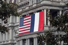 French and US flags hang on the Eisenhower Executive Office Building of the White House in Washington, Feb. 7, 2014.