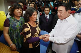After arriving from the Philippines, Amadeo Perez, chairman of the Manila Economic and Culture Office (MECO) in Taiwan, right, apologizes to the family of a Taiwanese fisherman killed by Filipino coast guard officers in Pingtung, southern Taiwan, Aug