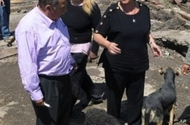 Chile's President Michelle Bachelet (r) talks to residents in a destroyed area of Concepcion, some 100 km (62 miles) south of the epicenter of a huge 8.8-magnitude earthquake that rocked Chile on February 27, 2010