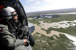Senior Chief Naval Air Crewman Xipetotec Thorngate searches, during a reconnaissance mission, inside an MH-60R Seahawk helicopter, aftermath of Hurricane Irma over Key West, Florida, U.S. on September 11, 2017.