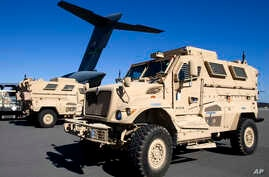 FILE - Mine-resistant, ambush-protected vehicles (MRAP), produced by Navistar, are loaded onto an airplane at Charleston Air Force Base in North Charleston, S.C.