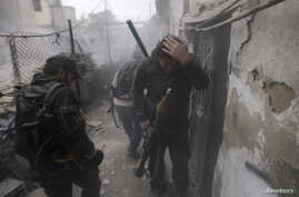 A Syrian rebel grabs his head as the smoke subsides, after the wall the group was taking shelter behind was hit by a shell fired from a government controlled army checkpoint, during fighting between the two sides in the Ain Tarma neighborhood of Dama
