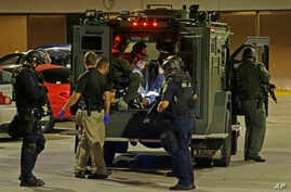 Armed police officers transport an injured man in an armored vehicle to a hospital Milwaukee, Aug. 14, 2016.
