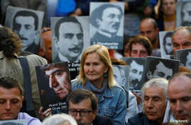 FILE - Human rights activists hold portraits of victims during a demonstration to commemorate the 1915 mass killing of Armenians in the Ottoman Empire, in central Istanbul, Turkey, Apr. 24, 2018.