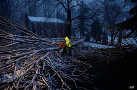 Streets department workers David Boardly, left, and James Ockimey clear a downed tree during a winter storm, March 2, 2018, in Marple Township, Pa.  A nor'easter pounded the Atlantic Coast with hurricane-force winds and sideways rain and snow Friday....