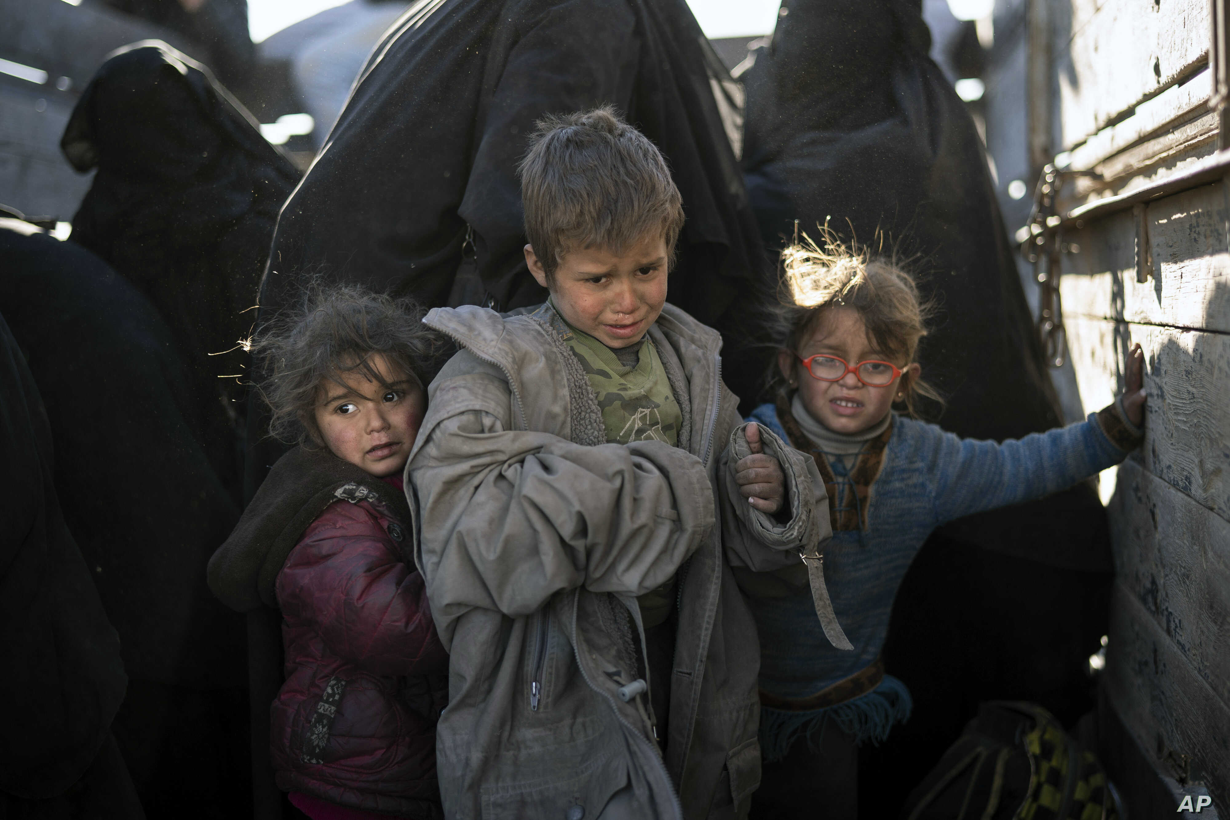Women and children exit the back of a truck as they arrive at a U.S.-backed Syrian Democratic Forces (SDF) screening area after being evacuated out of the last territory held by Islamic State militants, in the desert outside Baghuz, Syria, March 1, 2
