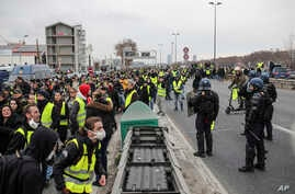 Demonstrators wearing yellow vests walk on the highway in Lyon, France, Jan. 5, 2019. Protesters reiterated their call for Emmanuel Macron, denounced as the president of the rich, to resign.