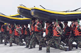 FILE - Navy SEAL trainees carry inflatable boats at the Naval Amphibious Base Coronado in Coronado, California, May 14, 2009.