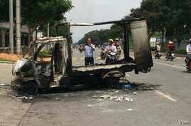 Passersby photograph a burned out vehicle after angry mobs burned and looted scores of foreign-owned factories in Vietnam. Many of the protesters are workers against China's recent placement of an oil rig in disputed Southeast Asian waters, officials