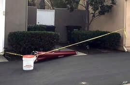 A piece of a helicopter that crashed into a house in Newport Beach, California, is cordoned off by police tape, Jan. 30, 2018.