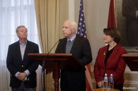 """U.S. Senators John McCain (C), Lindsey Graham (L) and Amy Klobuchar attend a news conference during their visit to in Riga, Latvia, Dec. 28, 2016. """"We must stand up to Vladimir Putin,"""" McCain said Sunday when the lawmakers visited Tbilisi, Georgia, a"""
