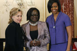 FILE - First lady Michelle Obama and Secretary of State Hillary Rodham Clinton present the 2010 International Women of Courage Award to Jestina Mukoko of Zimbabwe on March 10, 2010, at the State Department in Washington.