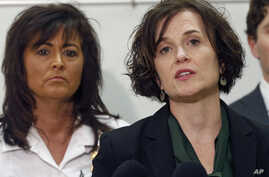 FILE - Minneapolis Police Chief Janee Harteau, left, listens as Mayor Betsy Hodges addresses a news conference, March 30, 2016, after the county attorney announced that no charges would be filed against two Minneapolis police officers in the fatal sh