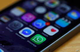 FILE - A WhatsApp icon (bottom, center) is seen on an iPhone in this March 27, 2017, illustration photo. WhatsApp is among the services subject to Uganda's social media tax.