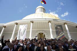 Deputies of Venezuelan coalition of opposition parties (MUD) pose for a picture in front of a giant picture of Venezuela's late President Hugo Chavez after a session of the National Assembly in Caracas, Jan. 5, 2016.