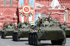 Russian servicemen aboard armored personnel carriers salute during the Victory Day parade in Moscow's Red Square, May 9, 2014.