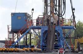 A crew works on a gas-drilling rig at a well site for shale-based natural gas in Zelienople, Pa., June 25, 2012.