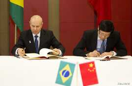Brazilian Minister of Finance Guido Mantega, left, and Chinese Minister of Finance Lou Jiwei sign a memorandum of understanding between countries, Durban, South Africa, March 26, 2013.