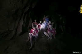 Boys from an under-16 soccer team and their coach wait to be rescued after they were trapped inside a flooded cave in Chiang Rai, Thailand, July 3, 2018, in this still image taken from a Thai Navy Seal handout video.