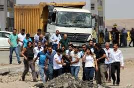 Paramedics and other people carry away a body after an explosion at a police station near the city of Diyarbakir, southeastern Turkey, Monday, Aug. 15, 2016.