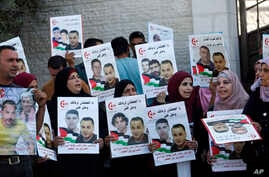 FILE - Palestinian demonstrators hold pictures of detainees as they take part in a protest in solidarity with Palestinian prisoners held in Israeli jails, in front of the United Nations headquarters in the West Bank city of Ramallah.