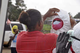 A health worker assists a colleague with his protective gear as they collect the body of a man suspected to have died from the Ebola virus in Monrovia, Liberia, Aug. 12, 2014.