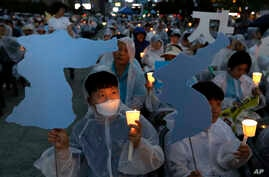 Participants hold candles and cardboard cutouts of the map of Korean Peninsula during a rally wishing for a successful summit between U.S. President Donald Trump and North Korea's leader Kim Jong Un, near the U.S. embassy in Seoul, South Korea, June