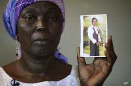 FILE-In this Monday, May 19, 2014 file photo, Martha Mark, the mother of kidnapped school girl Monica Mark cries as she displays her photo, in the family house, in Chibok, Nigeria.