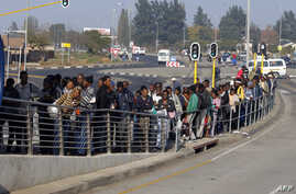 FILE - South African commuters line up at a bus stop in Soweto, May 17, 2010, during a strike by rail workers. Currently, a nationwide bus strike, in its fourth week, is causing similar lines to form for minibus taxis.
