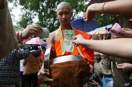 Followers offer banknotes to soccer team members as they are ordained as Buddhist monks and novices following their dramatic cave rescue last week in the Mae Sai district, Chiang Rai province, northern Thailand, July 25, 2018.