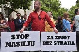 """Montenegro man holds banners reading """"Stop violence,"""" left, and """"For a life without fear,"""" right, during protest in Montenegro's capital, Podgorica, on Wednesday, May 9, 2018."""