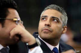 Canadian Al-Jazeera English journalist Mohammed Fahmy, listens to his lawyer, Khaled Abou Bakr during his retrial in a courtroom, of Tora prison, in Cairo, Egypt, June 1, 2015.