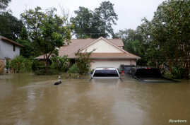 Houses and cars are seen partially submerged by flood waters from tropical storm Harvey in east Houston, Texas, U.S., Aug. 28, 2017.