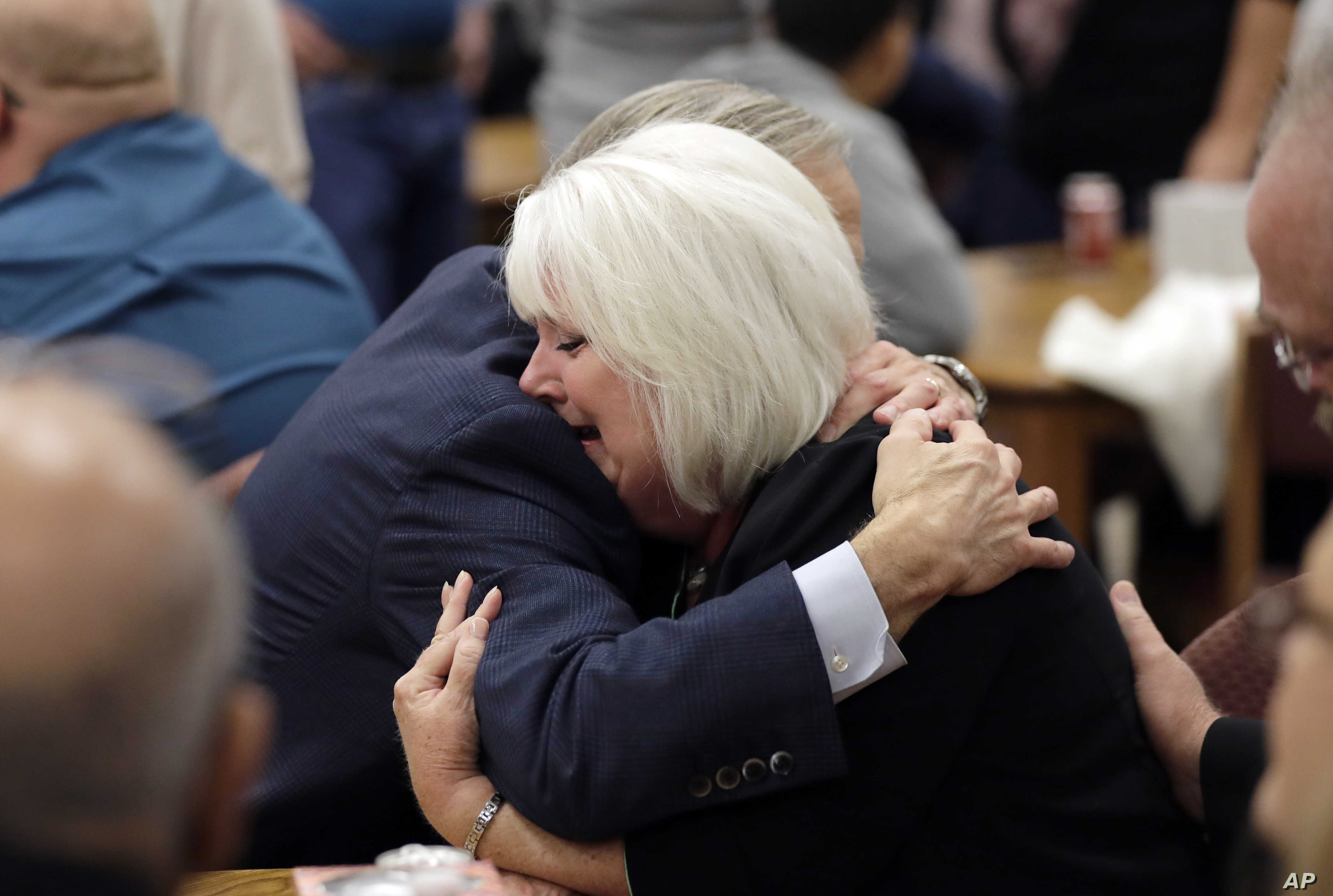 Texas Gov. Greg Abbott, left, hugs a woman as he visits with family and victims before a vigil, Nov. 8, 2017, in Floresville, Texas. A man opened fire inside a church in the small South Texas community of Sutherland Springs on Sunday, killing 26 woun