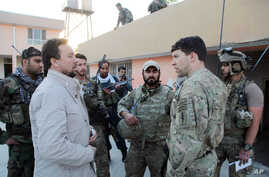 FILE - Kunduz chief of police, Mohammad Qasim Jangalbagh, left, talks to U.S. and Afghan special forces in Kunduz city, north of Kabul, Afghanistan, Oct. 1, 2015.