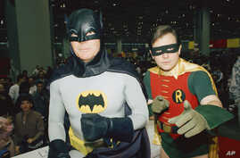 "FILE - Actors Adam West, left, and Burt Ward, dressed as their characters Batman and Robin, pose for a photo at the ""World of Wheels"" custom car show in Chicago, Jan. 27, 1989."