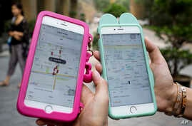 Women holding their smartphones show the ride-hailing apps Uber Technology Ltd., left, and Didi Chuxing at a residential compound in Beijing, Aug. 1, 2016.