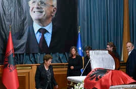 Xhemajlie Demaci, wife of human rights defender Adem Demaci, walks by his coffin in parliament's hall, in Pristina, July 27, 2018.