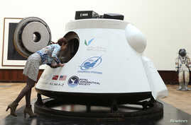 An employee at the Lempertz Auction House looks into in a Soviet capsule Vozvrashchayemyi Apparat in Brussels.