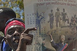 A man holds a calendar depicting Haiti's ousted President Jean-Bertrand Aristide during a protest in Port-au-Prince, Haiti, February 18, 2011